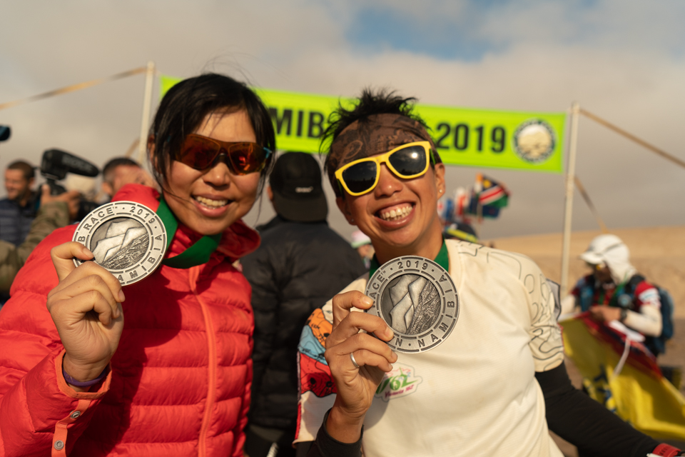 Smiling and showing off their medals